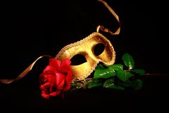 Golden Mask. A golden mask resting on a rose Stock Images