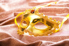 Golden mask on the satin Stock Photos