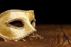 Golden mask on wooden table Stock Image