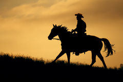 A golden meadow horseback ride. A cowboy rides at sunset in a golden grass meadow stock photos