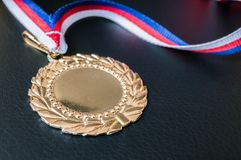 Golden medal for first place on black background Royalty Free Stock Photos