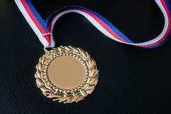 Golden medal for first place on black background Stock Photography