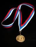 Golden medal isolated on black. Golden sport medal isolated on black royalty free stock photography