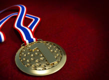 Golden medal on the red background. Stock Photography