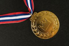 Golden medal Sport competition with red  blue and white ribbon o. N  black background Royalty Free Stock Photography