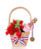 Golden medal and tulips. A golden medal on a bottle champagne with tulips in a wicker basket isolated over white royalty free stock photo