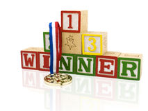 A golden medal for the winner. A golden medal with ribbon hanging over a pile of blocks with 1,2,3 and the letters winner on it in red, green and yellow stock photography