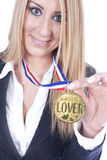 Golden medal winner. A beautiful blond is showing worlds best lover medal Stock Image