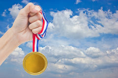 Golden Medal In Woman Hand. Golden Medal In Woman Hand With Blue Sky Stock Photography