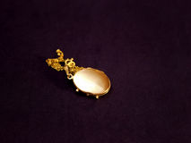 GOLDEN MEDALLION. BEAUTIFUL OLD GOLD MEDALLION ON BLACK CLOTH,PHOTOGRAPHY Stock Photos