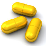 Golden medical capsules 3d Stock Images