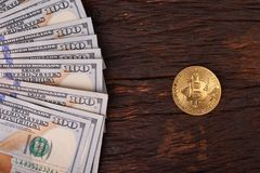 Golden metal bitcoin on dollar bills background. a lot of money in cash. 100 dollars texture. dear bitcoin. Gold coin. Profit from. Mining stock photos