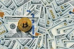 Golden metal bitcoin on dollar stock photo