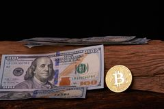 Golden metal bitcoin on dollar bills background. a lot of money in cash. 100 dollars texture. dear bitcoin. Gold coin. Profit from stock image