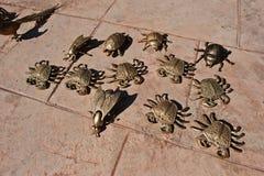 Golden metal figures of sea crabs, scarab beetle stock image