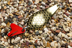 Golden metal fishing bait for a spinning on the stony ground Stock Image