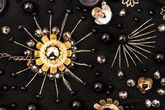 Golden metal flower with crystal beads around on fabric Royalty Free Stock Photography