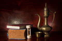 Golden metal jug with antique books and hourglass. Stock Image