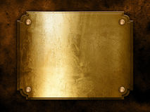 Golden metal plate on concrete wall Stock Images