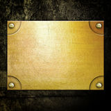 Golden metal plate on concrete wall Royalty Free Stock Photos