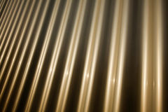 Wavy Metal Background. Golden metal squiggly wall in the sunlight Stock Image