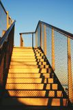 Golden metal stairs towards the roof under blue sky. Golden stairs towards the roof under blue sky at the sunset. Thank you for your DOWNLOAD Royalty Free Stock Photos