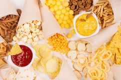 Golden mexican colorful snacks - nachos, popcorn, croutons, chips in craft paper cone with  spiced sauces on white wood table. Golden mexican colorful snacks Stock Photo