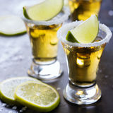 Golden mexican tequila shot with green lime and salt Stock Images