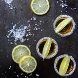 Golden mexican tequila shot with green lime and salt Stock Photography