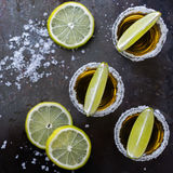 Golden mexican tequila shot with green lime and salt Royalty Free Stock Image
