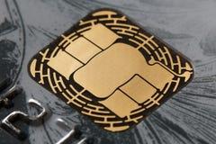 Microchip on credit card. Golden microchip on a gray credit card closeup Stock Photos