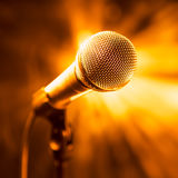 Golden microphone on stage. With rays background Stock Image