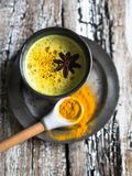 Golden milk with curcuma powder in the blue ceramic glass on a wood background, Strengthening health and stimulating immunity. A stock images