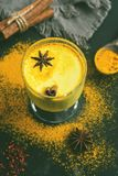 Golden milk with turmeric powder in glasses on a dark rustic background. Health and energy boosting, flu remedy,warming drink. Cle royalty free stock images