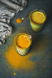 Golden milk with turmeric powder in glasses, energy boosting drink Royalty Free Stock Image