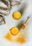 Golden milk with turmeric powder in glasses over grey background Royalty Free Stock Image