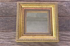 Golden mirror with baroque frame on wooden background Royalty Free Stock Photography