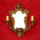Golden mirror with two candlesticks. Antique classic golden mirror with two candlesticks on a red fabric background Stock Image
