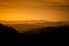 Golden misty silhouetted hills at dawn Stock Images