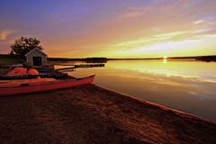 Golden moment. Red Kayaks on the beach, calm waters, golden sunset Royalty Free Stock Photos