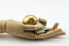 Golden and money nest egg metaphor. Golden nest egg in palm of wooden hand with dollar notes isolated on white Royalty Free Stock Photo