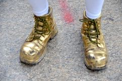 Golden Mummer Slippers. A pair of gold painted shiny shoes worn by a mummer in the Philadelphia Mummers Parade on New Years Day royalty free stock photo