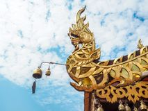 Golden naga statue on roof of temple with blue sky background stock image