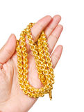 Golden necklace in left hand. Royalty Free Stock Image