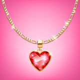 Golden necklace with ruby heart on chain. Royalty Free Stock Photo