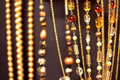 Golden necklaces and gems, shallow dof on black. A set of golden necklaces shot at shallow depth of field on black royalty free stock images
