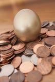 Golden nest egg. Golden egg nested on pile of coins Stock Photography