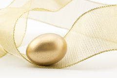 Golden nest egg in swirl of gold ribbon. Gold nest egg placed in swirl of golden metallic ribbon creates sense of movement, excitement, and success Stock Photo