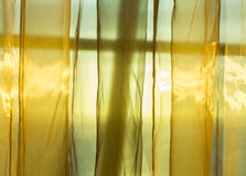 Golden net curtains shield sunshine behind window. Sunlight from outside window streams into a room through thin golden silky net curtains Royalty Free Stock Images
