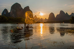 Golden nets. Lijiang in Guilin, Guangxi, China, a fisherman fishing on fishing boats in the sunset under the mapping, fishing net flashing golden light, the stock photography